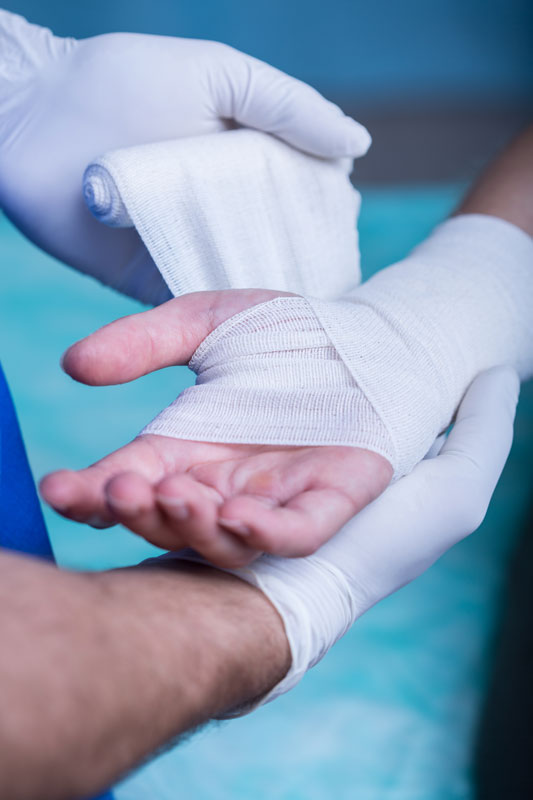 Bandaged patient hand held by occupational therapist